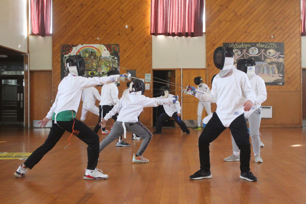 Two rows of fencing students, practicing basic hits